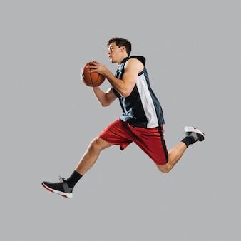 Homem pulando enquanto segura uma bola de basquete