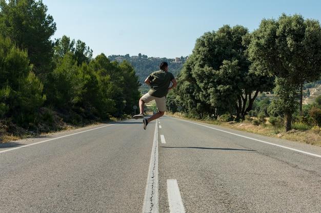 Homem pulando na estrada vazia. globetrotter