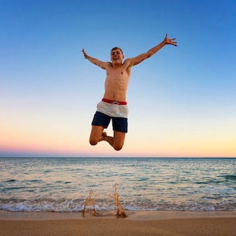 Homem pulando na praia do camilo, portugal