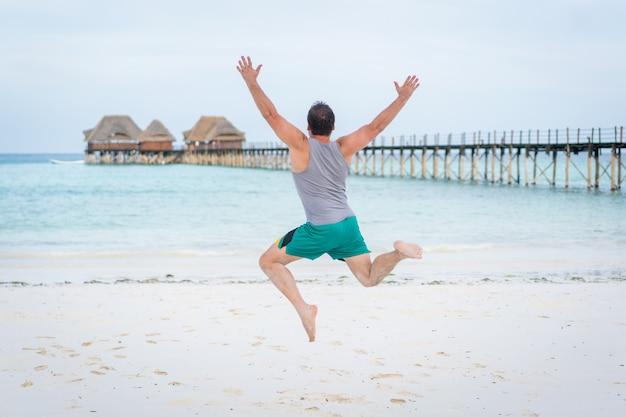 Homem pulando na praia tropical