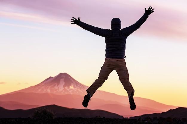 Homem pulando nas altas montanhas ao pôr do sol