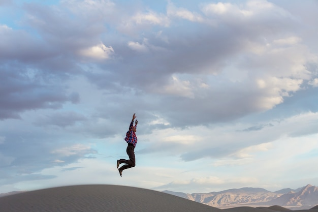 Homem pulando nas dunas de areia ao pôr do sol