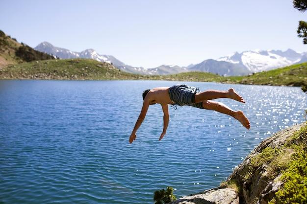 Homem pulando no lago com altas montanhas rochosas