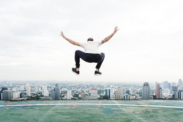Homem pulando no telhado