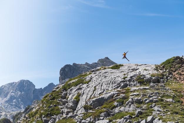 Homem pulando no topo de uma montanha com fundo de céu azul.