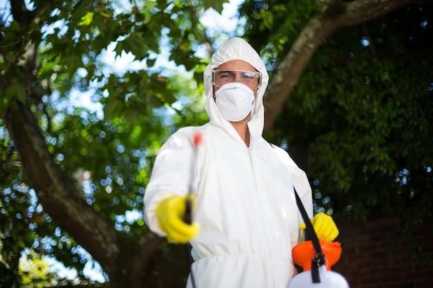 Homem pulverizando inseticida em pé contra uma árvore