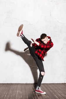 Homem punk na camisa, fazendo um chute alto