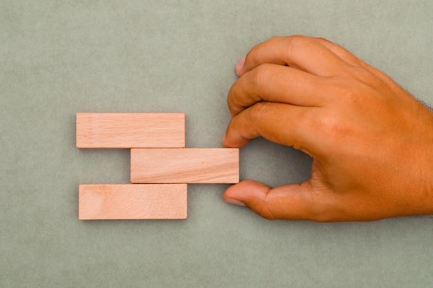 Homem puxando blocos de madeira