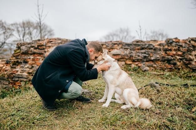 Homem que abraça o husky ao ar livre.
