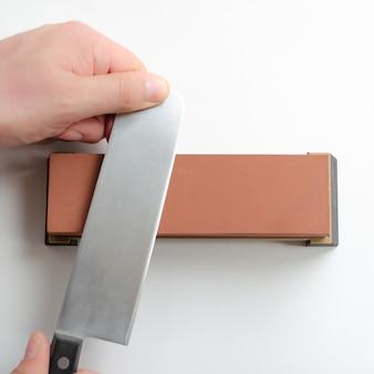 Homem que afia uma faca nakiri japonesa com apontador de pedra de amolar ou rebolo no espaço em branco