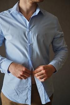 Homem que ajusta seus botões de camisa.