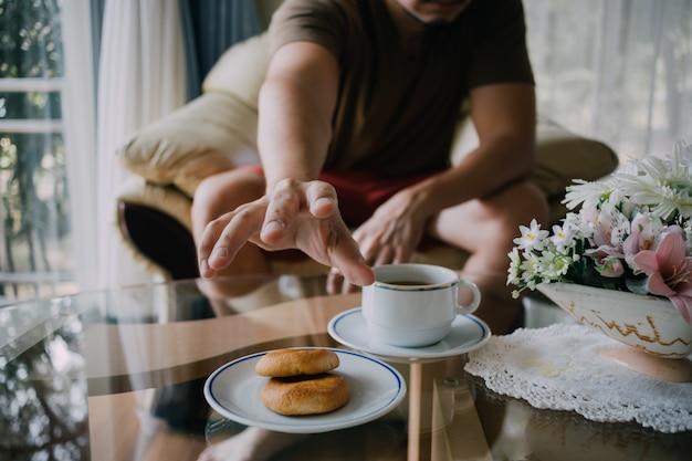 Homem que alcança para agarrar cookies e café.