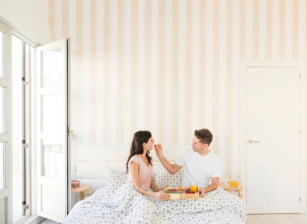 Homem que alimenta mulher com bagas durante o café da manhã