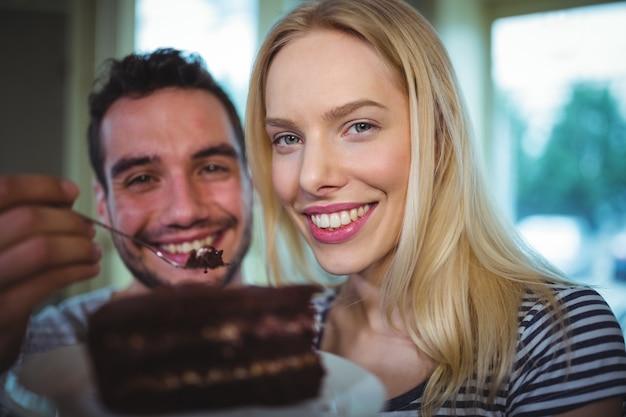 Homem que alimenta pastelaria a mulher em cafã ©