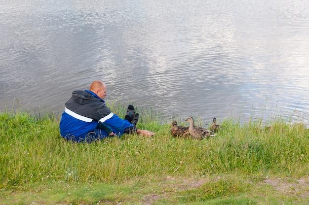 Homem que alimenta patos em uma lagoa. o socorrista alimenta os patos, os patos famintos têm medo de se alimentar das mãos.