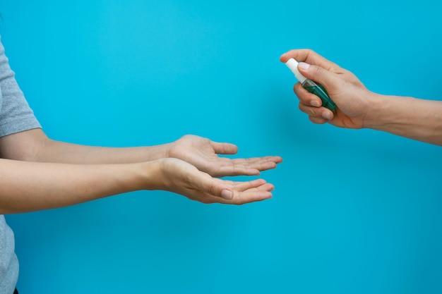 Homem que aplica gel desinfetante nas mãos de sua esposa para proteção contra vírus infeccioso, bactérias e germes em fundo azul
