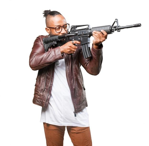 Homem que aponta para o lado dele com metralhadora