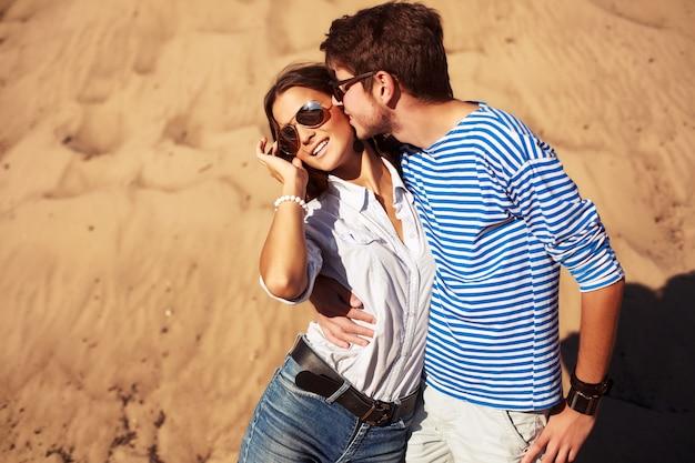 Homem que beija e abraça sua amiga na praia