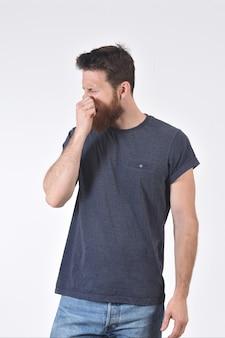 Homem que cobre o nariz com os dedos porque faz um cheiro ruim