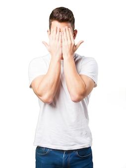 Homem que cobre o rosto com as mãos