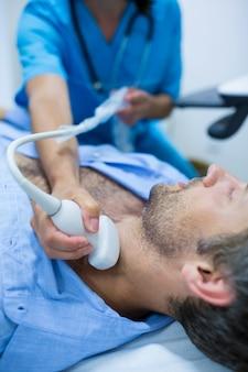 Homem que começ o ultra-som de um tiróide de médico