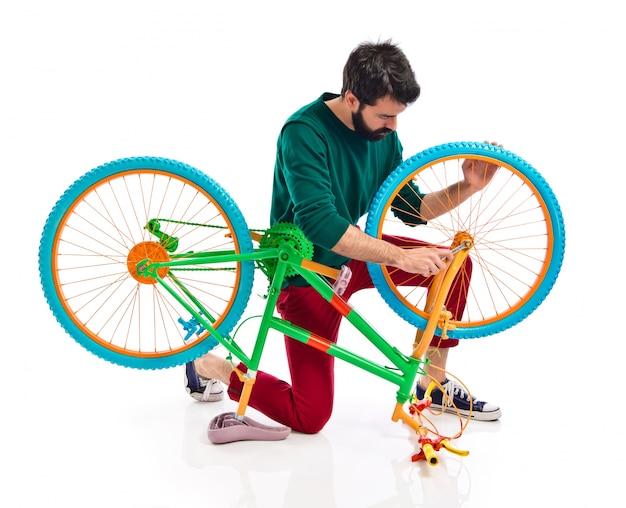 Homem que conserta uma bicicleta
