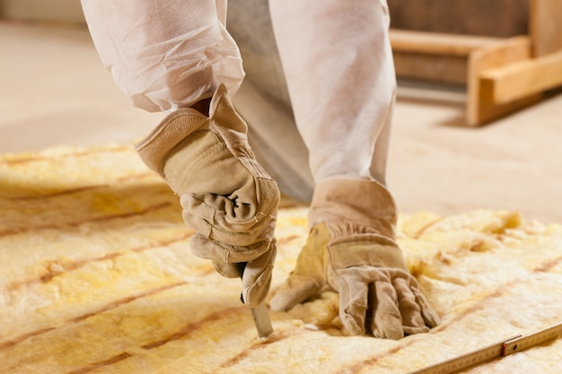 Homem que corta o material de isolação para a construção