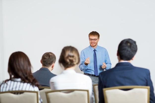 Homem que dá uma palestra para uma audiência
