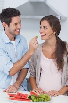 Homem que dá uma uva à sua parceira grávida