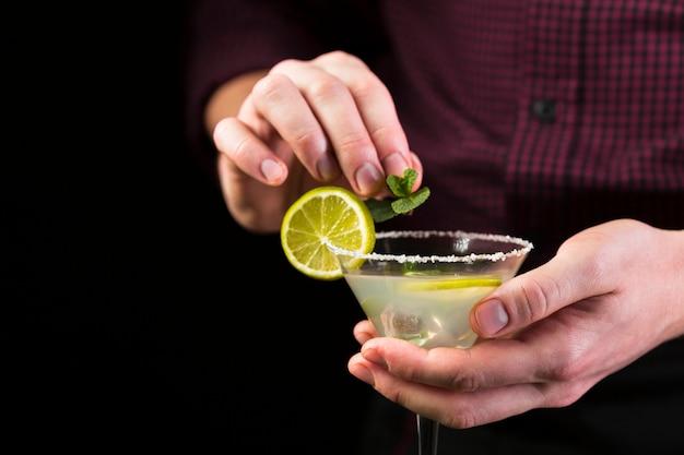 Homem que decora o copo de cocktail com hortelã