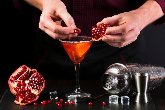 Homem que decora o copo de cocktail com romã