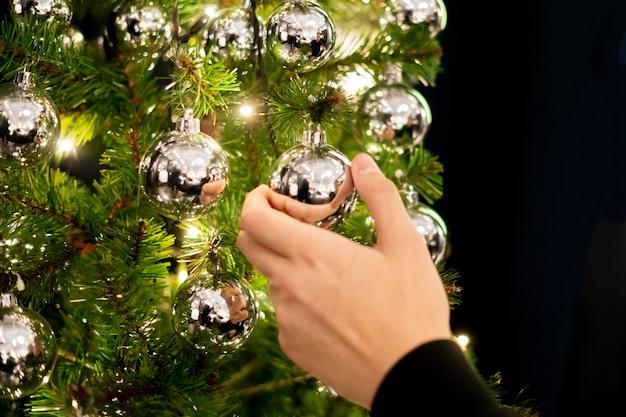Homem que decora o pinheiro do ano novo do natal com bolas em casa