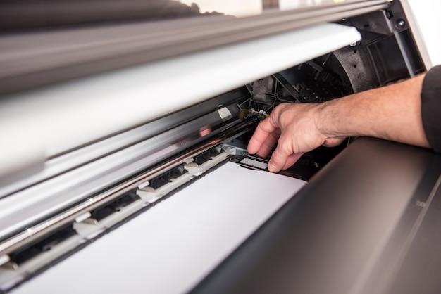 Homem que define a impressora para a largura do papel