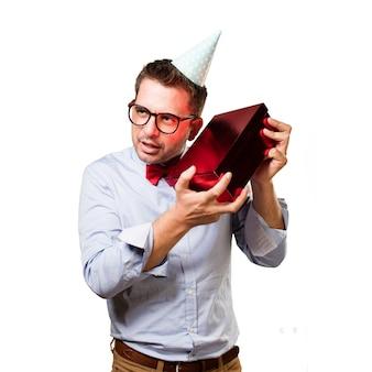 Homem que desgasta um chapéu de laço e vermelho do partido. segurando presente.