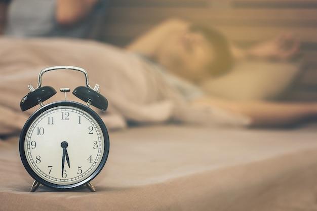 Homem que dorme sem acordar de manhã com o despertador no dia útil.