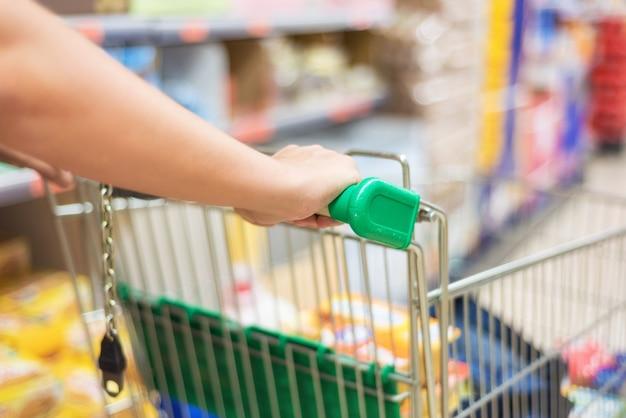 Homem que empurra o carrinho de compras no fundo do borrão do sumário da loja do supermercado.