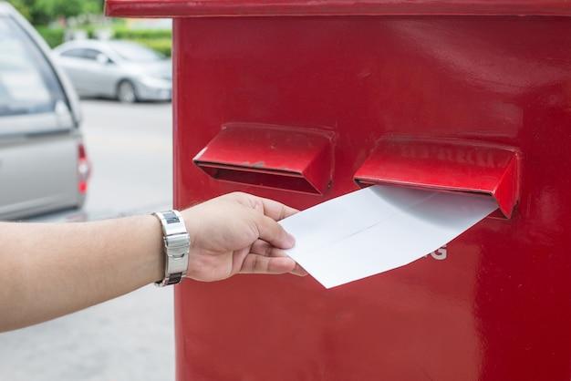 Homem que envia o correio na cidade. um homem enviando uma carta e documentos via caixa de correio.