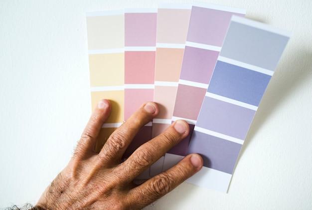 Homem que escolhe a cor da parede escolhendo de uma amostra da cor
