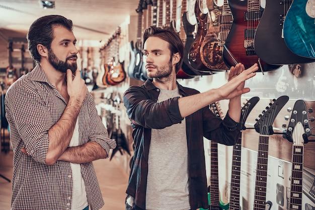 Homem que escolhe a guitarra elétrica na loja do instrumento musical.