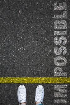Homem que está na marcação amarela da pintura de estrada que divide a linha entre im e possível como a palavra impossível.