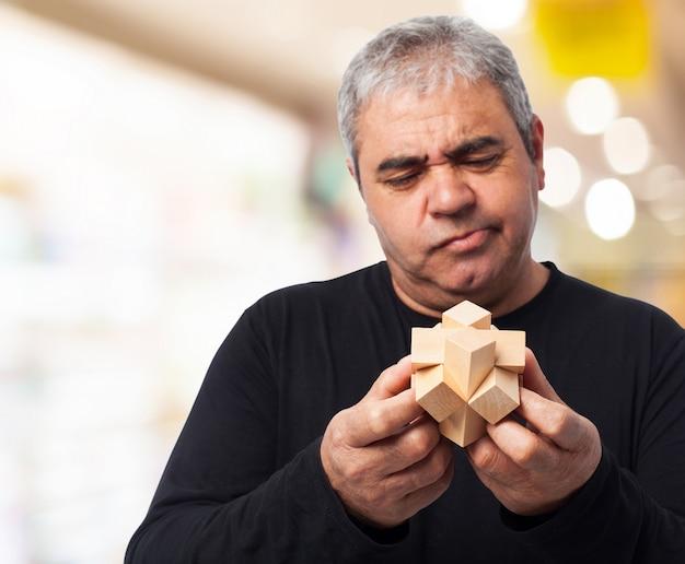 Homem que examina a figura de madeira