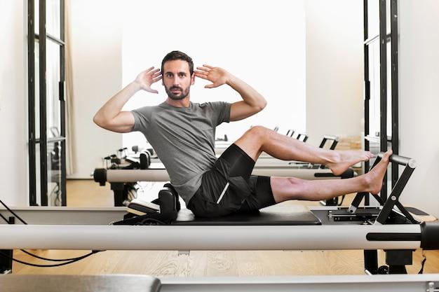 Homem que executa um trecho de perna única de pilates