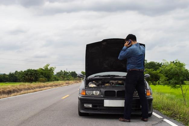 Homem que fala em um smartphone quando carro quebrado na estrada.