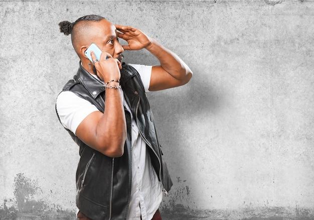 Homem que fala no telefone com a mão na testa