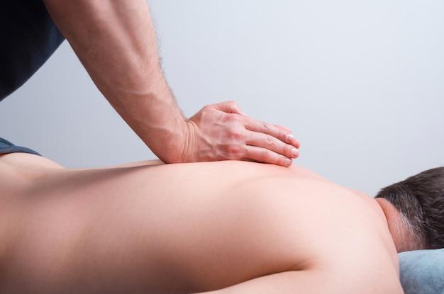 Homem que faz a cinesiologia fazer massagens no fundo branco.