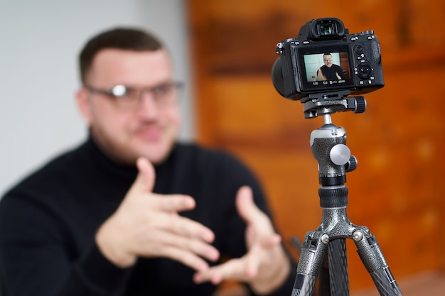 Homem que filma o blog de vídeo na câmera com tripé para seguidores on-line. nas mídias sociais, influenciador, nova tecnologia e conceito de internet