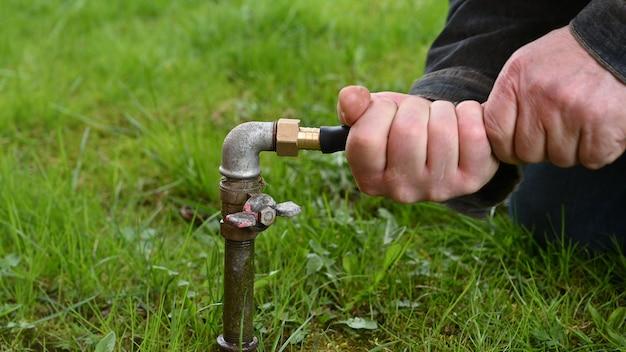Homem que fixa a tubulação de água do jardim.