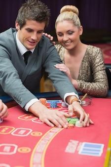 Homem que ganha no poker com uma mulher ao lado dele