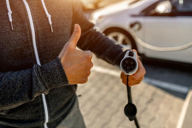 Homem que guarda o cabo de carregamento do poder para o carro elétrico no parque de estacionamento exterior. o motorista um polegar para cima