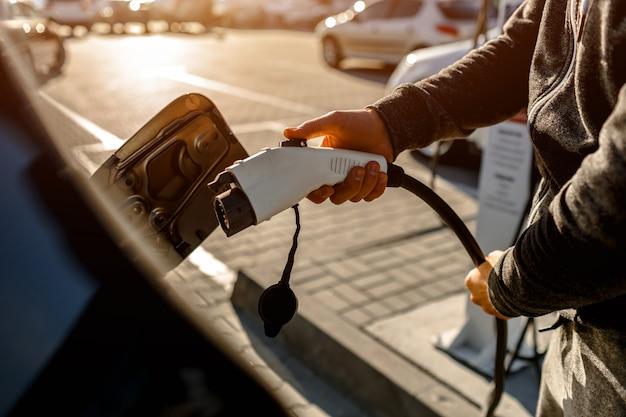 Homem que guarda o cabo de carregamento do poder para o carro elétrico no parque de estacionamento exterior.